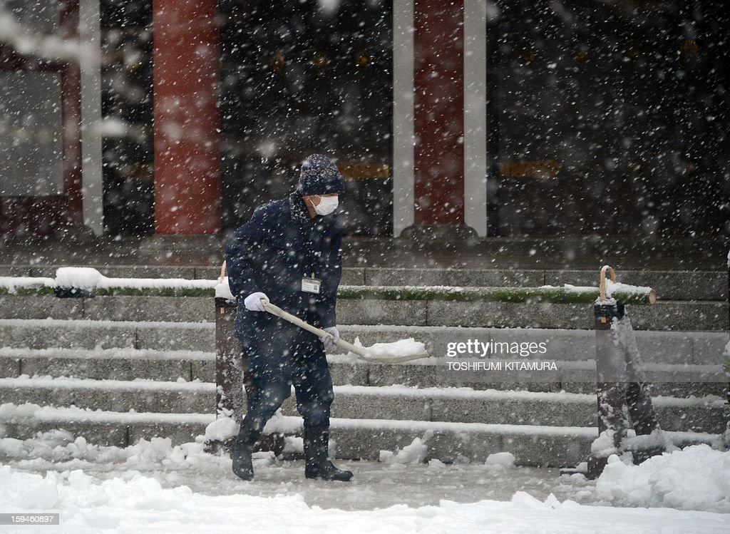 A worker shovels snow at Sensoji temple in the Asakusa area in Tokyo on January 14, 2013. A storm system grasped central Japan on January 14, causing heavy snow fall around the Japanese capital.