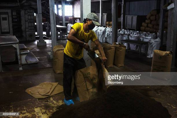 A worker shovels tea into bags at the packing section of the Makaibari Tea Estate factory in Kurseong West Bengal India on Monday Sept 8 2014 The...