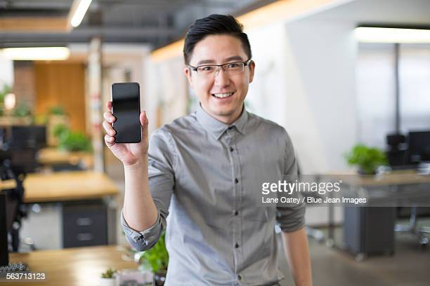 IT worker showing smart phone in office