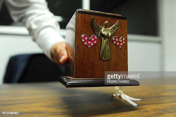 A worker shows a funeral urn found in a wagon of the metro at the lost property office of the Candelaria transport system station in Mexico City on...