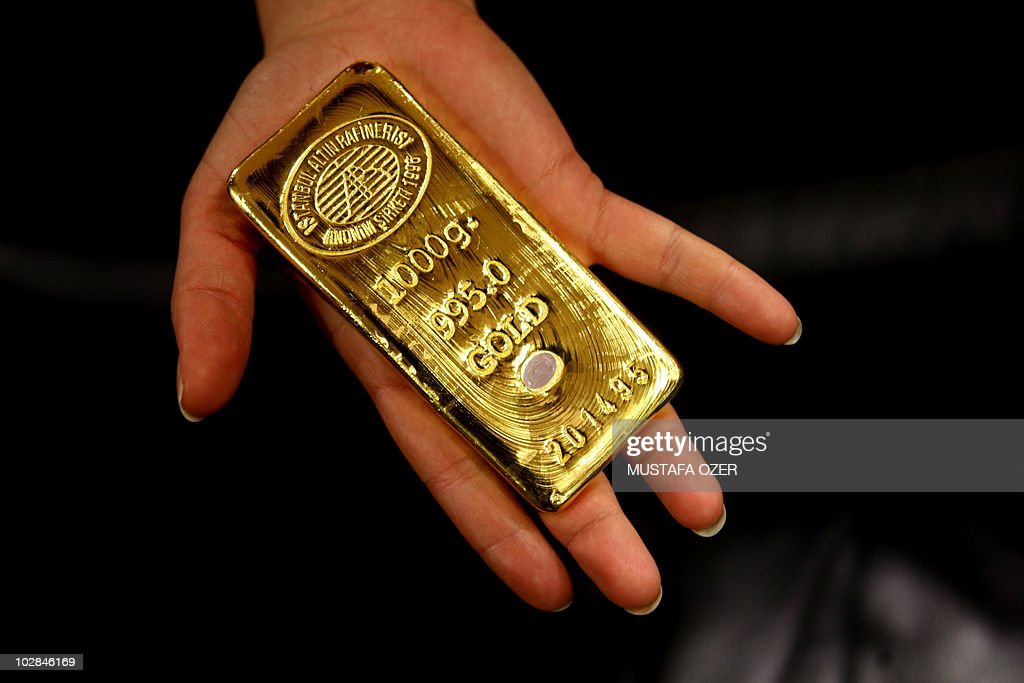 A worker shows a gold bar ready for sale in Istanbul Gold Refinery, after being melted in the refinery, on February 10, 2009. After the Turkish Lira gained in value against the gold price, Turkish people start selling their homestocked gold.