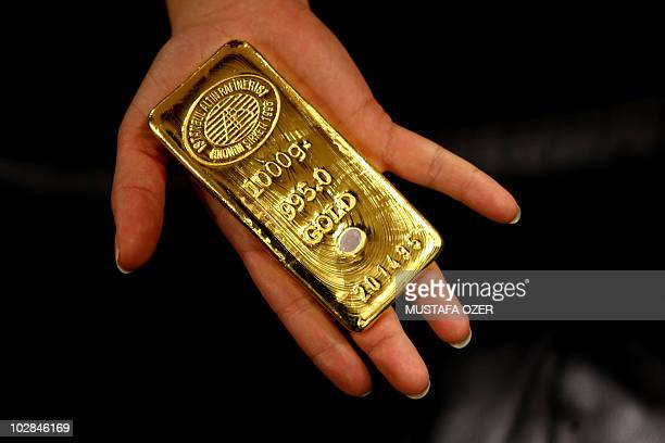 A worker shows a gold bar ready for sale in Istanbul Gold Refinery after being melted in the refinery on February 10 2009 After the Turkish Lira...