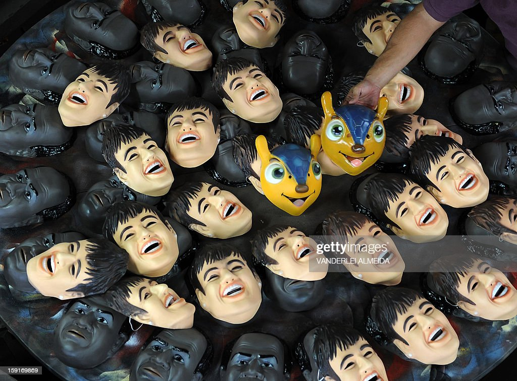 A worker shows masks of Brazilian football star Neymar, the president of the Brazilian Supreme Court Joaquim Barbosa and the mascot of the Brazil 2014 FIFA World Cup, 'Tatu Bola-Fuleco', at the carnival masks factory Condal, in Sao Gonçalo, about 35 km from downtown Rio de Janeiro, on January 9, 2013. Rio's world famous carnival takes place February 9-12. AFP PHOTO/VANDERLEI ALMEIDA