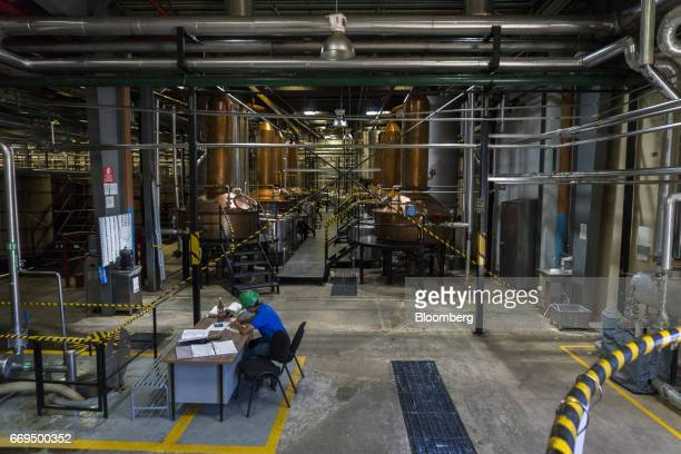 A worker sits at a desk in front of copper pot stills at the Patron Spirits Co distillery in Atotonilco El Alto Jalisco Mexico on Tuesday April 4...