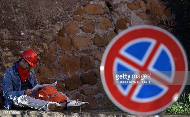 A worker sits during a demonstration organised by Italian General Confederation of Labour union on October 25 2014 in central Rome as part of a...