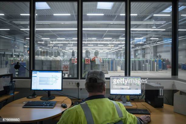 A worker sits in the control room as empty canisters stand beyond inside the Linde AG compressed gas plant in Marl Germany on Monday Nov 20 2017...