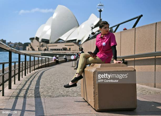 A worker sits on a bollard newly installed to help protect tourists and locals from a terror attack at the Sydney Opera House on September 20 2017 A...