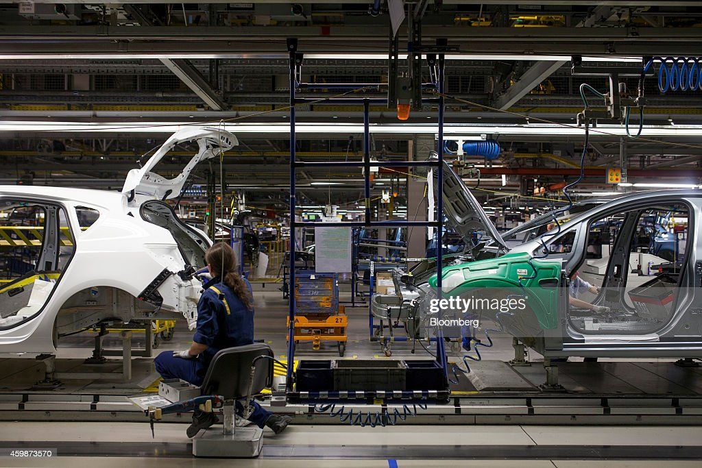 A worker sits on an hydraulically operated chair during the assembly of Opel Astra automobiles on the production line at General Motors Co's Adam...