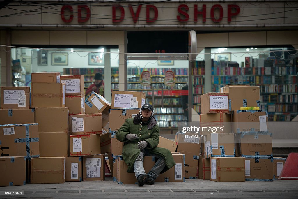 A worker sits on boxes outside a DVD shop in Beijing on January 11, 2013. China's inflation rate slowed sharply in 2012, official data showed, but analysts warned of increasing price risks this year that may limit scope for measures to boost economic growth. AFP PHOTO / Ed Jones