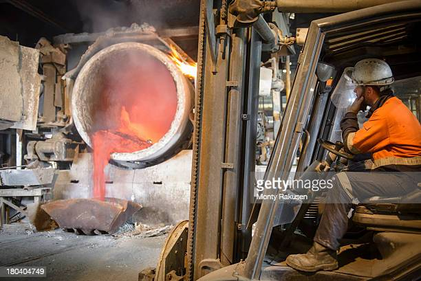 Worker sitting in forklift truck watching furnace in aluminium foundry
