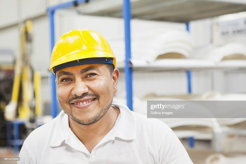 Worker smiling in manufacturing plant : Stock Photo
