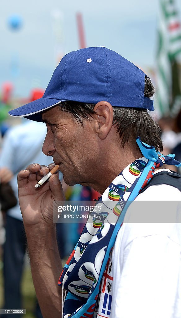 A worker smokes a cigarette as he follows speeches by the three main italian trade unions CGIL,CISL and UIL during a demonstration for work and tax fairness in Rome's Piazza San Giovanni in Laterano on June 22, 2013. AFP PHOTO/ Filippo MONTEFORTE
