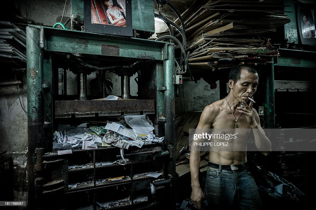 A worker smokes a cigarette at a waste paper collection outlet in Hong Kong on September 25, 2013. While the former British colony already recycles around half of its waste, its per capita generation of domestic waste remains significantly higher than other leading Asian cities, including Tokyo, Seoul and Taipei. AFP PHOTO / Philippe Lopez