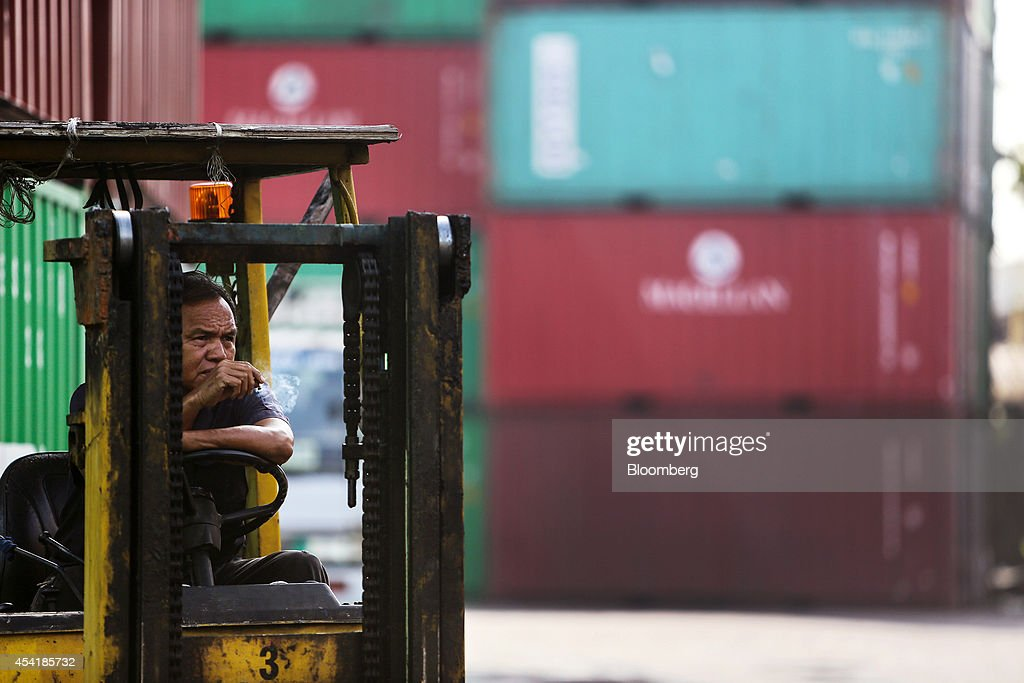 A worker smokes while sitting in forklift truck next to stacked containers at the Custom Global Service Co. container depot in Bangkok, Thailand, on Monday, Aug. 25, 2014. Thailand's trade figures are scheduled for release on Aug. 27. Photographer: Dario Pignatelli/Bloomberg via Getty Images