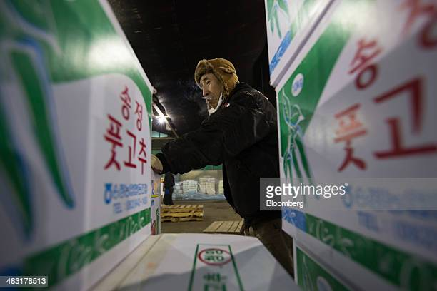 A worker smoking a cigarette moves a box of green peppers at Garak Market operated by Seoul AgroFisheries Food Corp in Seoul South Korea on Wednesday...