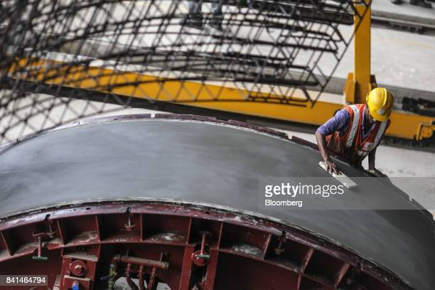 A worker smooths the surface of a precast concrete tunnel segment as it sits in a mold at the Mumbai Metro Rail Corp casting yard in Mumbai India on...