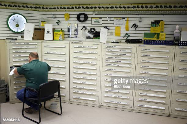 A worker sorts Deere Co John Deere farm machinery parts at the Smith Implements Inc dealership in Greensburg Indiana US on Wednesday Aug 16 2017...