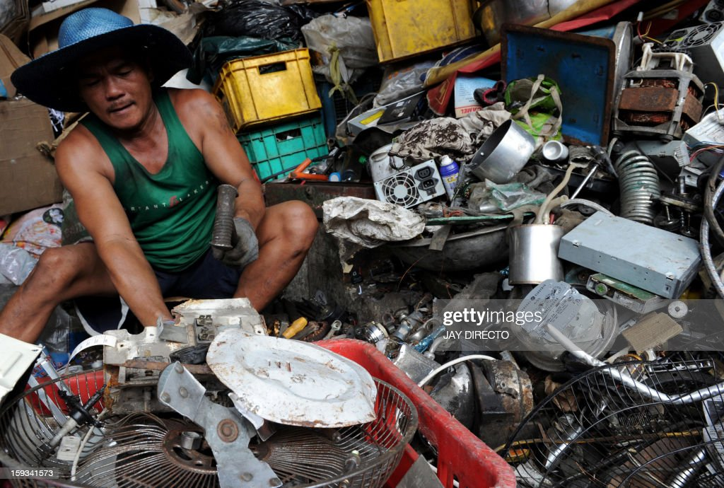 A worker sorts discarded recyclable materials into different kinds of metals in a junkshop in Manila on January 12, 2013. The shop buys different kinds of recyclable materials from metal to papers and plastics which are used to make new materials. AFP PHOTO / Jay DIRECTO