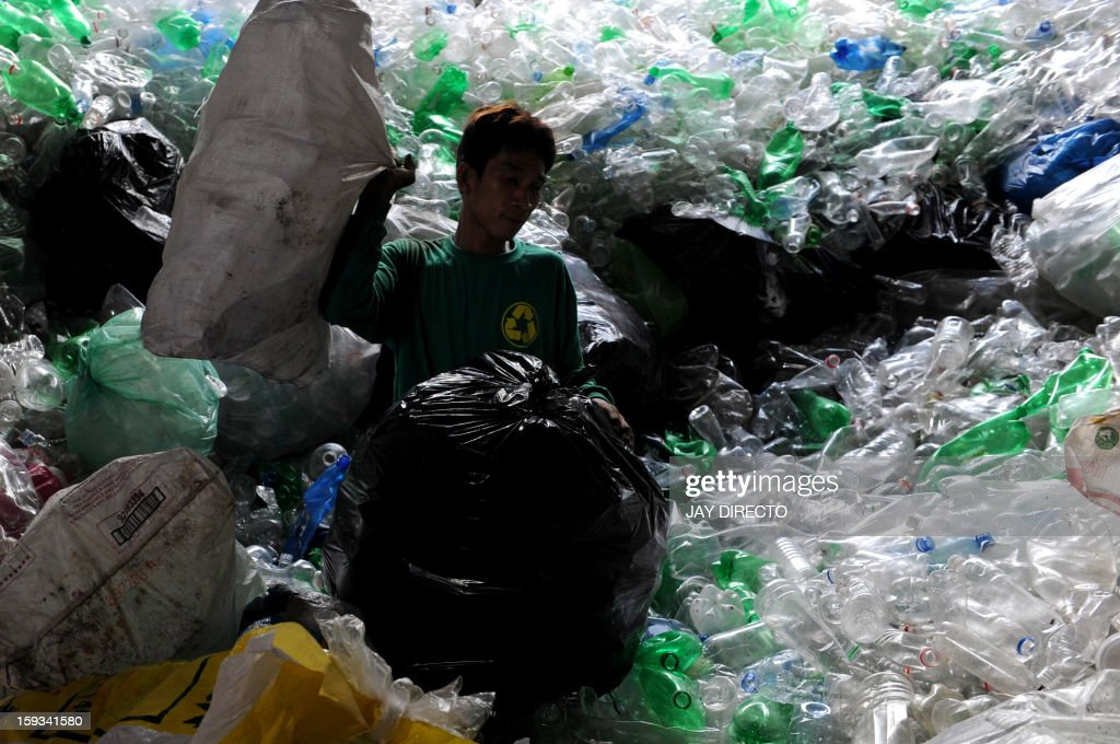 A worker sorts discarded recyclable materials into different kinds of plastics in a junkshop in Manila on January 12, 2013. The shop buys different kinds of recyclable materials from metal to papers and plastics which are used to make new materials. AFP PHOTO / Jay DIRECTO