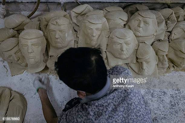 A worker sorts out masks of Donald Trump on the floor at the Shenzhen Lanbingcai Latex Crafts Factory on October 18 2016 in Shenzhen China Shenzhen...