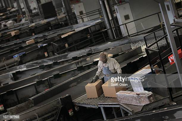 A worker sorts packages at a UPS facility on November 29 2010 in Hodgkins Illinois Shippers have geared up for the holiday shipping rush which is...