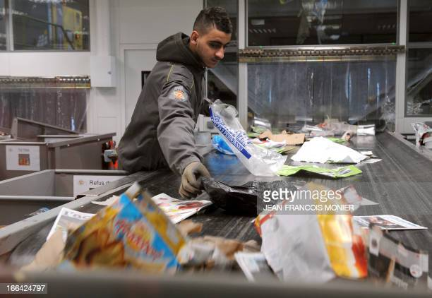 A worker sorts papers and packaging in the recycling plant of waste ValorPôle 72 on April 12 2013 in Le Mans western France ValorPôle 72 is a...