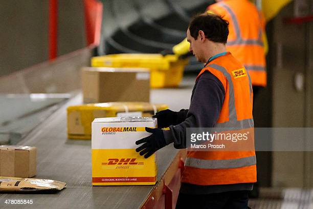 A worker sorts parcels during the night at the DHL hub on February 27 2014 in Leipzig Germany The soon to be expanded hub handles 2000 tons of cargo...