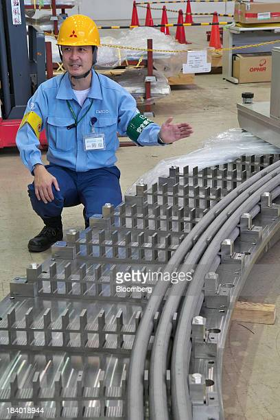 A worker speaks to the media near a winder for toroidal field coils at Mitsubishi Heavy Industries Ltd's Kobe Shipyard Machinery Works Futami Plant...