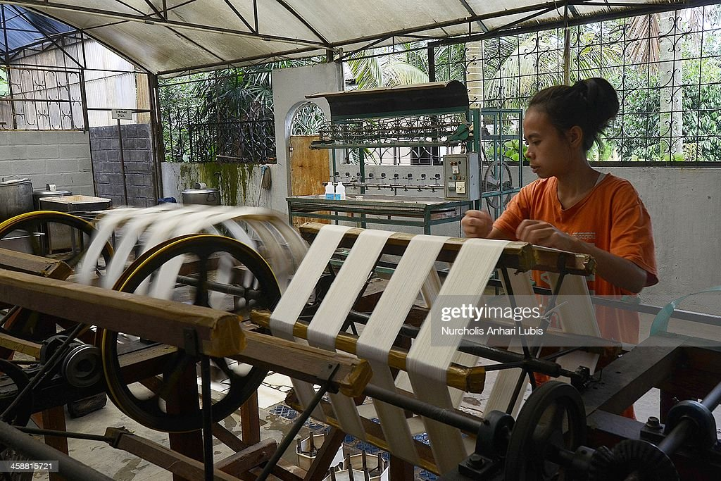 A worker spins silk into thread at a production unit on December 21, 2013 in Bogor, Indonesia. The Indonesian silk industry is well established although generally consisting of small and local producers in contrast to more developed competition and industry seen in countries such as Japan, China and Thailand. The silk produced is used in the manufacture of traditional handicrafts including batik clothing and textiles.