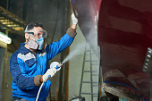 Side view portrait of  worker wearing protective mask spray painting boat in yacht workshop  copy space