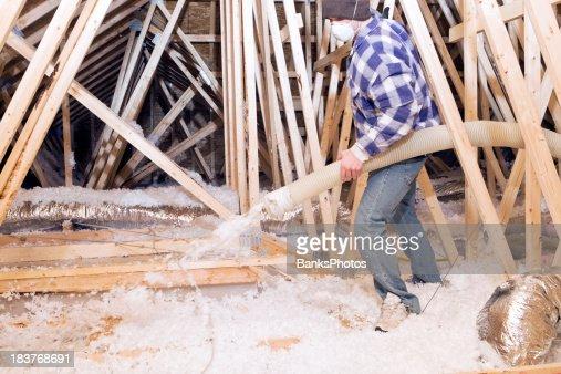 Worker spraying blown fiberglass insulation between attic for Blow in insulation vs batts