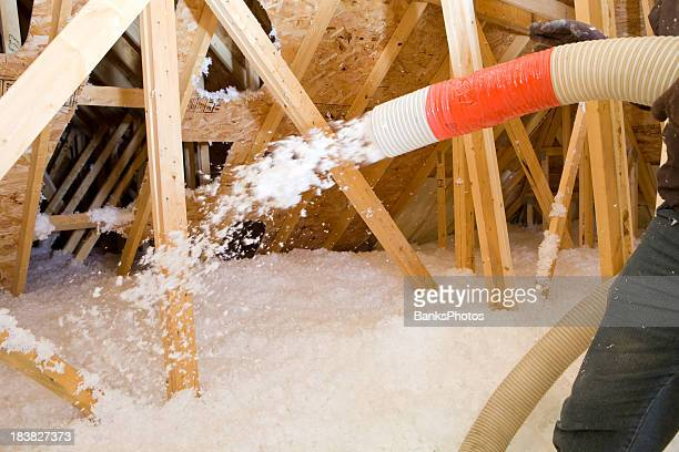 Worker Spraying Blown Fiberglass Insulation between Attic Trusses