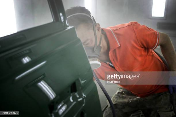 Worker spraying bonnet at paint room of mehenic garages in Paju South Korea A 20yearold beat up Hyundai SUV isn't anyone's idea of a dream car But...