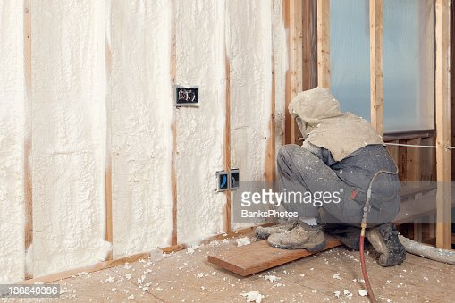 Worker Spraying Expandable Foam Insulation between Wall Studs