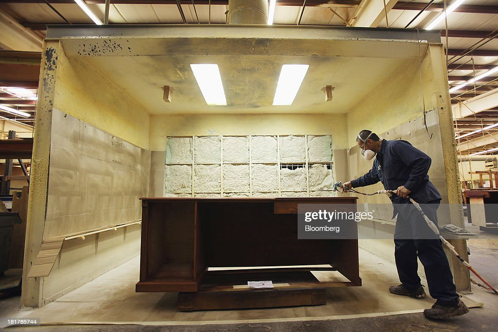 A Worker Sprays A Clear Finish Onto A Custom Piece Of Furniture At The At  Baker