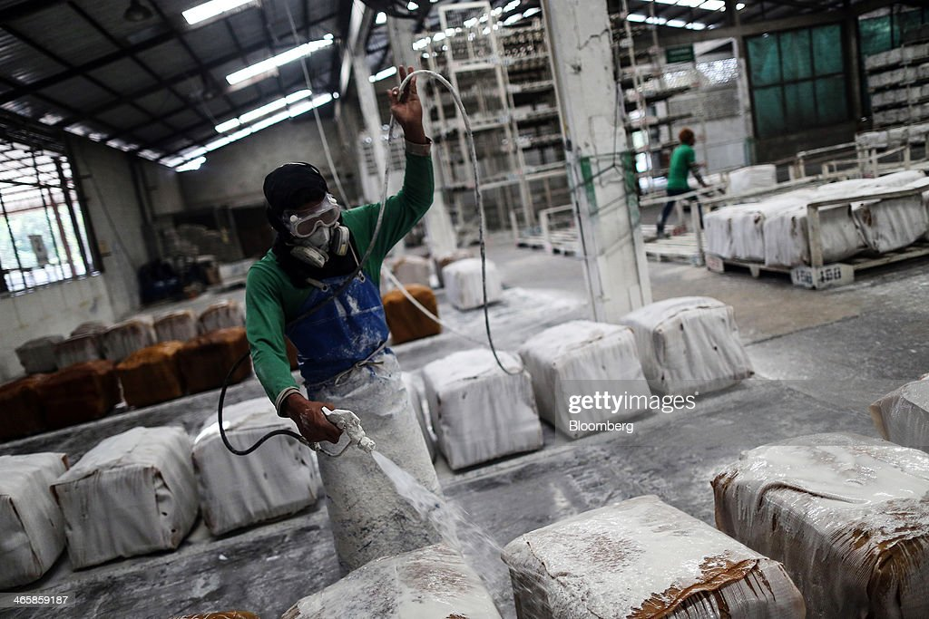 A worker sprays bundles of smoked rubber sheets with a calcium carbonate solution, used as a resist and to prevent molding, before being packaged for shipment at the Thai Hua Rubber Pcl factory in Samnuktong, Rayong province, Thailand, on Wednesday, Jan. 29, 2014. Rubber production in Thailand, the world's largest exporter, may decline as growers from the main producing regions join protests seeking to overthrow the government, according to Von Bundit Co. Photographer: Dario Pignatelli/Bloomberg via Getty Images