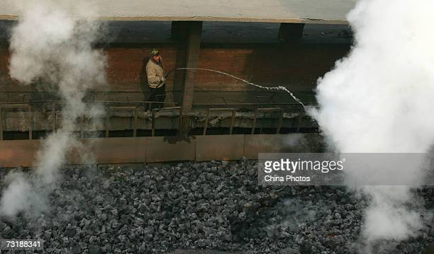 A worker sprays down water to cool down coke at the Xian Coking Factory which will be shut down while the local government launches a campaign to...