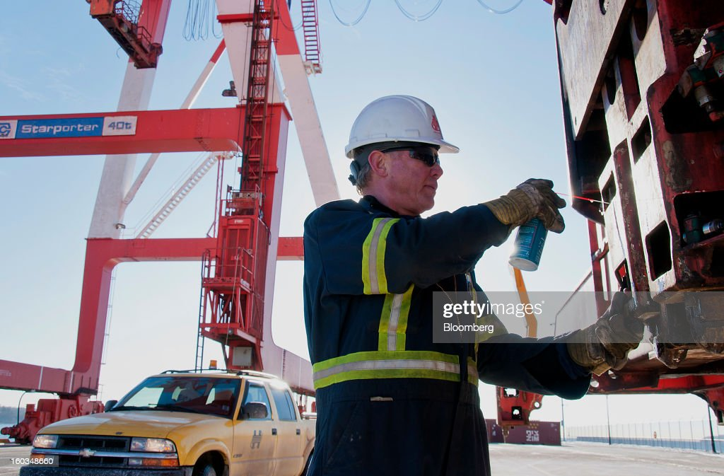 A worker sprays lubricant on gears at the Port Of Halifax's South End container terminal, operated by Halterm Ltd., in Halifax, Nova Scotia, Canada, on Tuesday, Jan. 29, 2013. Statistics Canada (STCA) is scheduled to release gross domestic product data on Jan. 31. Photographer: Aaron McKenzie Fraser/Bloomberg via Getty Images