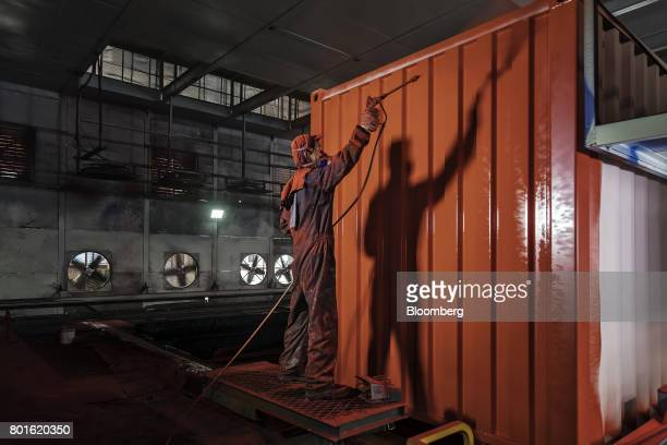 A worker sprays paint onto a shipping container in the paint shop at the SingamasContainer Holdings Ltd factory in Qidong China on Thursday June 22...
