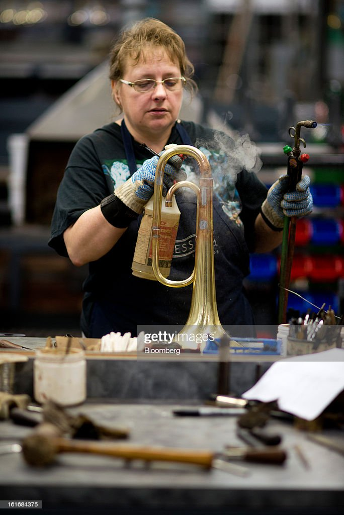 A worker sprays water on the hot tubes of a brass mellophone to cool it off during assembly in the manufacturing department of the E.K Blessing Co. in Elkhart, Indiana, U.S., on Thursday, Feb. 7, 2013. Photographer: Ty Wright/Bloomberg via Getty Images