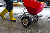 worker pushing salt spreader on icy New York City sidewalk during snow storm in winter.