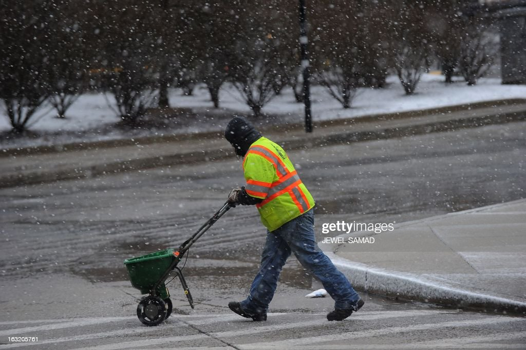 A worker spreads salt on a walkway in Silver Spring, Maryland, on March 6, 2013. A massive winter storm pounding the northern US on March 6, grounded 2,600 flights, closed hundreds of schools and made roadways and highways impassible. At least four people were reportedly killed in accidents on icy and snow covered roads and highways. AFP PHOTO/Jewel Samad