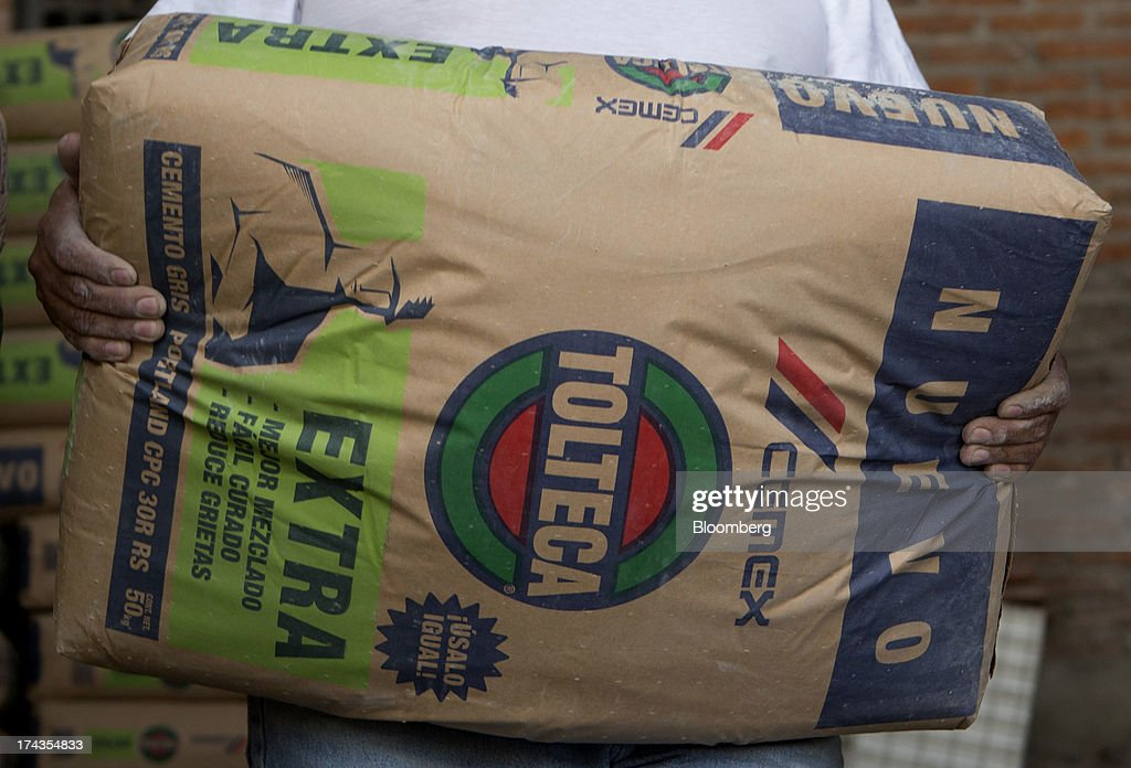 A worker stacks bags of Cemex SAB's Tolteca brand cement at a distribution center in Barrientos in the state of Mexico on Wednesday, July 24, 2013. Mexican President Enrique Pena Nietos $320 billion infrastructure plan is reviving a rally in cement maker Cemex SABs bonds after the emerging-market rout derailed an advance fueled by the U.S. housing rebound. Photographer: Susana Gonzalez/Bloomberg via Getty Images