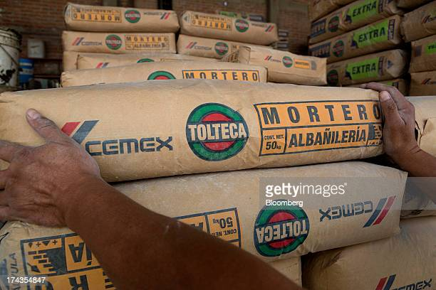 A worker stacks bags of Cemex SAB's Tolteca brand cement at a distribution center in Barrientos in the state of Mexico on Wednesday July 24 2013...