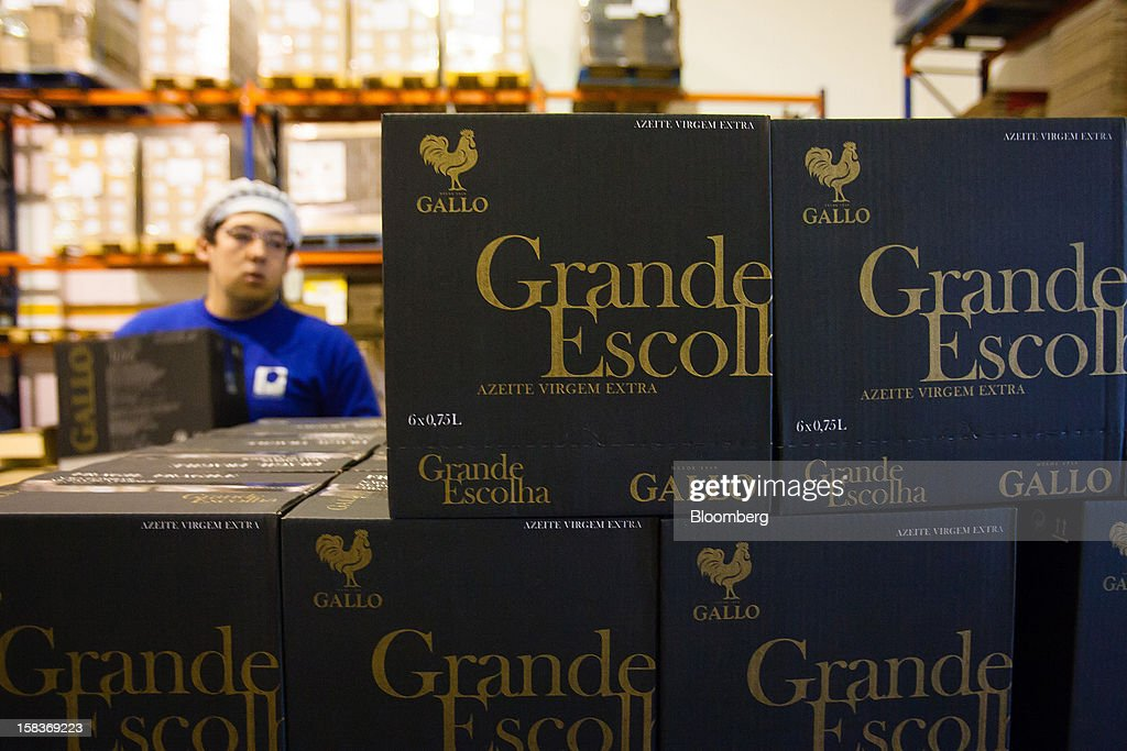 A worker stacks boxes of special selection olive oil at the Gallo Worldwide plant in Abrantes, Portugal, on Friday, Dec. 14, 2012. The Iberian nation has already been granted more time to narrow its budget shortfall after tax increases failed to bring in enough money to meet forecasts as the economy heads for a third year of contraction in 2013. Photographer: Mario Proenca/Bloomberg via Getty Images