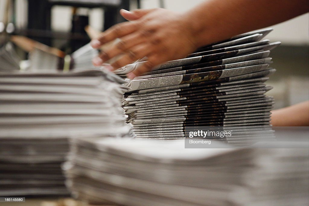 A worker stacks copies of the Los Angeles Times newspaper after printing at the Olympic Press facility in Los Angeles, California, U.S, on Wednesday, Oct. 16, 2013. Congress ended the 16-day government shutdown, raising the U.S. debt limit after the leaders of the Senate reached a bipartisan agreement to end the nation's fiscal impasse. Photographer: Patrick T. Fallon/Bloomberg via Getty Images