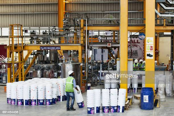 A worker stacks empty paint containers at an Akzo Nobel India Ltd factory in Gwalior Madhya Pradesh India on Thursday June 1 2017 Akzo Nobel NV...