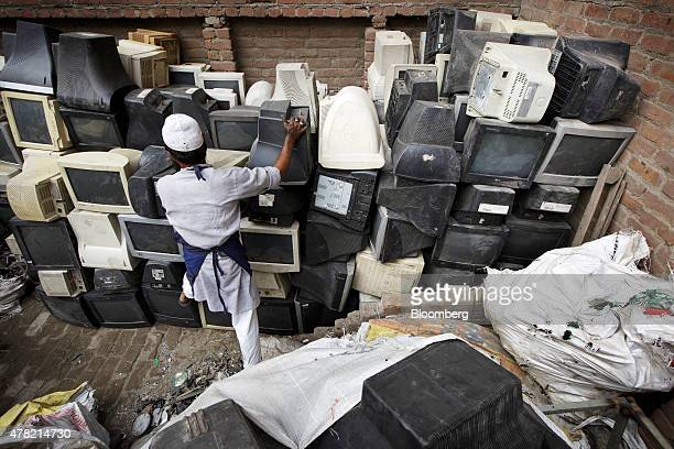 A worker stacks used computer monitors at a workshop in New Delhi India on Thursday June 18 2015 The rupee climbed 08 percent in the five days ended...