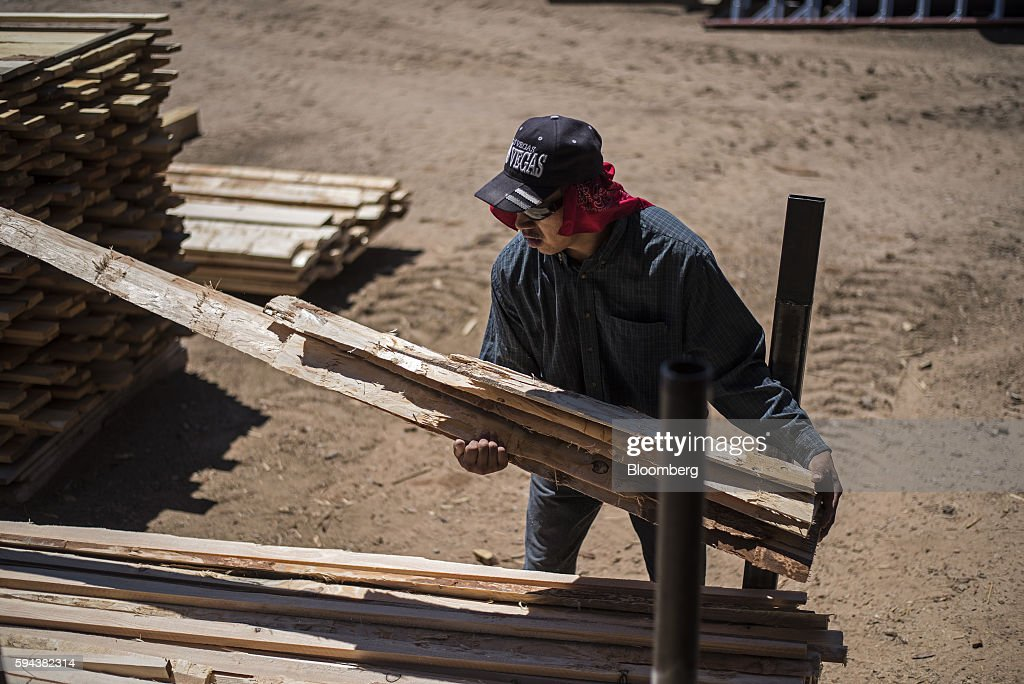 A worker stacks wood planks at the Spotted Owl Timber Inc mill in Santa Fe New Mexico US on Monday Aug 15 2016 Founded in 1991 the family owned and...