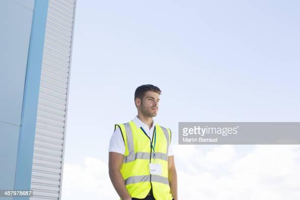 Worker standing below highrise building